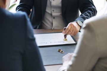 Avocat qui officialise avec un tampon un certificat de divorce devant un couple