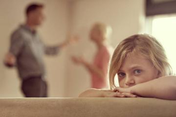 enfant triste avec parents qui se disputent en arrière plan